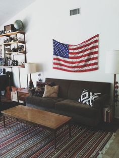 "living room with ""old glory"" flag hanging I place of artwork above the sofa"