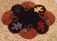 Primitive wool penny rug fall pumpkin candle mat doily on Etsy, $49.99