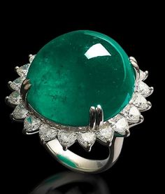 A cabochon emerald and diamond ring The oval cabochon emerald, weighing 61.32 carats, surrounded by a frame of heart-cut diamonds between tapered shoulders to a plain hoop, the diamonds estimated to weigh approximately 4.70 carats in total.
