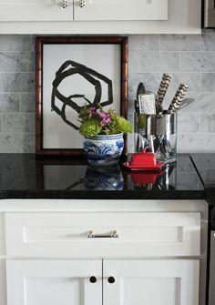 Marble backsplash, black counters, light cabinets