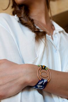 This one-of-a-kind wrap bracelet was sewn by a female genocide survivor working at the Aspire co-cop in Rwanda. Traditional Rwandan fabric in a colorful medley of bright blue, purple, green and orange. The mandorla, a powerful ancient symbol of wholeness, was handmade using recycled copper in San Diego, CA. #gift