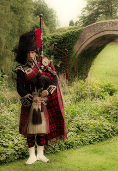 """Piper at """"Brig o' Doon"""" in Alloway, Ayrshire. The Brig o' Doon is a late medieval bridge used as the setting for the final verse of the Robert Burns's poem Tam o' Shanter."""