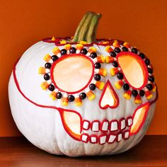 """Sweet Skulls  Use a white pumpkin or paint the pumpkin white, let dry. Carve out large eyes, a heart-shaped nose and """"hollowed"""" cheeks. Use E6000 craft glue (available at craft stores) to apply candy: use M and candy corn around the eyes, red licorice ropes as outlines, and square white gum for teeth."""