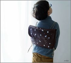 NEW COLLECTION 2017.   Kids Vintage Inspired Backpacks.  This retro style backpack is made of dark brown faux leather, covered with handprinted white leaves and glands. Sweet and simple style of this satchel makes it perfect as a kindergardenbag or unique fashion accessory for your kids. Inside there is a compartment to put some of your babys the most favourite treasures for everyday adventures. The retro design is completed with two special antique finish brass trims. Dimensions of the…
