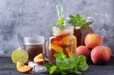 Peach ice tea in the jars - Peach ice tea in the jars served with peaches, lime, mint leaves and decorated with ice cubes over black stone background