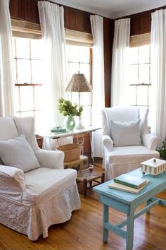 Work WITH wood paneling: Long, flowing drapes and bright, white chairs give this paneled room a breezy, beachy feel. This fix doesn't involve any messy paint, and adds light texture to a space. See more at The Lettered Cottage Cottage Living, Home And Living, Cozy Living, Deco Champetre, Living Comedor, Small Places, Slipcovers, Family Room, Living Spaces