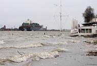 3656_0734 Wellen schlagen auf den Strand bei Hochwasser an der Strandperle in Hamburg Oevelgönne; die Sonnenschirme sind zusammengefaltet, Tische und Stühle gesichert. Ein Containerschiff verlässt den Hamburger Hafen, es wird mit Hilfe von Schleppern in die Fahrrinne gebracht.
