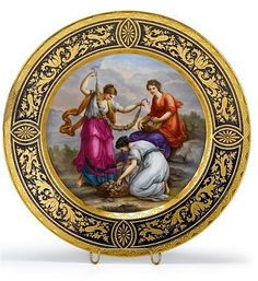 Vienna 'jeweled' porcelain cabinet plate late 19th century Painted with a scene of three classical maidens arranging floral garlands, within a gilt decorated cobalt border, blue beehive mark to reverse and inscribed 'Flora'.