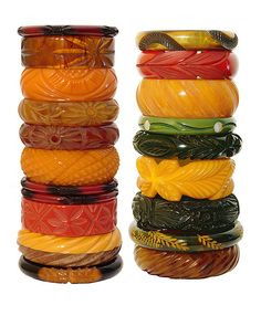 An assortment of bangles made of cast Phenolic Resin, a plastic also known as Bakelite or Catalin. Hand made from Bakelite tubes cut, carved and polished and sometimes dyed by artisans. These tubes were about the same height of these stacks. The mix with other materials was common, as seen here with wood and mother-of-pearl. These bangles were in fashion from 1930 to after the war.  They all have the standard inner measure of 2 and a half inches.