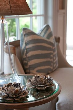 love the white and blue zebra pillow paired with mirrored top accent table fileld with tall crystal lamp with burlap lamp shade and clam shell votive holders.