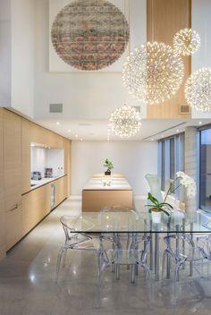 Sin duda esta cocina es muy elegante y moderna ..... Pero como la hacen a si ...... Pues la madera con blanco le da un toque moderno espectacular ..... Y ni se hable de las lamparas colgantes y la mesa con las sillas transparentes ..... También el techo de luces empotradas la hace demasiado genial ...... Y moderna elegante