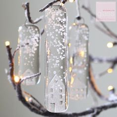 """This set of three""""Snowy glass houses"""" will look magical hung on a Christmas tree or in a window. Each decoration has an embossed house with falling glass snow and come with a small metal hook for hanging. Your glass will come in a white box packaged with white tissue paper. 10cm by 2 cm 8cm by 2cm 6cm by 2 cm"""