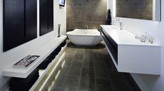 De mørke marmorklinker er ført fra gulvet og videre op på endevæggen i forældrenes badeværelse. Skodderne langs den ene væg rummer to indbyggede Fengshui-skabe. Badekarret af corian hedder Scoop og håndvasken, der hedder Shape, er italiensk. Armaturet fra Vola er sensor- styret. Håndklæderne er fra Eva Solo.
