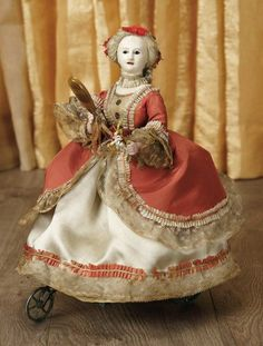"""11"""" Early French Mechanical Glidin...Marks: Vichy a Paris. Comments: Vichy, Paris, circa 1850. Value Points: when wound, the elegant lady glides forward and circles while turning her head and lifting arms alternately; especially beautiful coiffure and original costume."""