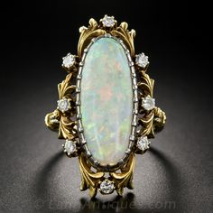 A singular and gorgeous antique opal ring dating from the first decade of the twentieth century is artfully hand crafted in two-tone white and yellow gold flourished with scrolling foliate motifs primped with eight sparkling round-cut diamonds. The dreamy