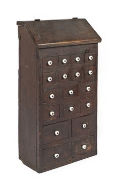 Pennsylvania walnut apothecary cupboard, early 19th c., with eighteen drawers under a canted lid, 30 1/2'' h., 16'' w., 8'' d.