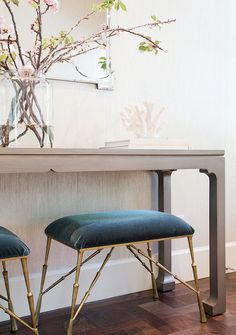 Stunning foyer features a wall lined with platinum gray textured wallpaper lined with a pair of turquoise velvet stools tucked under a gray console table topped with cherry blossoms placed in front of a Greek key mirror.