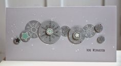 handmade winter card ... short and wide #10 format ... shades of gray with spots of aqua ... snowflakes stamped on medium gray and puched out in circles of various sizes ... circles form a sinuous band ... wonderful mod look ....