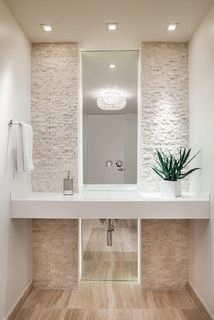 The floor to ceiling rock tile and mirrors give this powder room a spa-like feel.