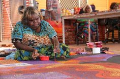An Aboriginal artist from the Amata community in the APY Lands works on a dot painting. (Photo: ABC/Natalie Whiting)