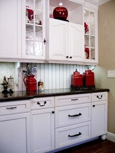 White kitchen, black granite, red accents.