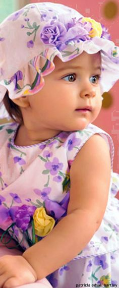 Aletta wearing a cute purple flowered hat and matching outfit.