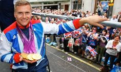 Heavy metal: quadruple gold medal winning Paralympian David Weir takes holds his medals on top of his float.