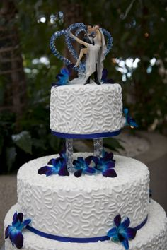 top tier of a royal blue wedding cake decorated with white chocolate butter cream, satin ice fondant, cornelli lace and blue Singapore orchids