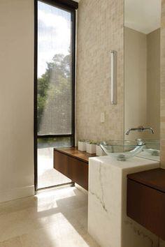 Linhas retas, boa iluminação, tons de bege e madeira e vidro - um banheiro moderno.