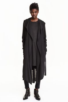 Crêpe coat: Double-breasted coat in a lightly crêped weave with a hood, side pockets, concealed press-studs at the front, an asymmetric hem with a slit at the back and a tie belt. Unlined.
