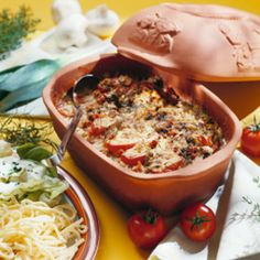 Römertopf wässern. Fleisch in feine Streifen schneiden, salzen, pfeffern. Kochschinken in feine Würfel schneiden. Tomaten überbrühen, enthäuten und...