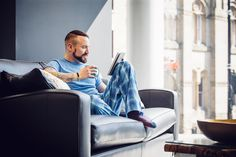 A man in his late 20s is sitting at home on the sofa in his pajamas searching the web on his digital tablet.