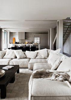 Iso sohva oleskelutiloissa, keittiö taustalla.
