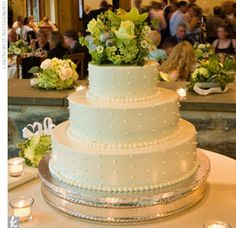 three-tier ivory cake adorned with Swiss dots and an arrangement of fresh green flowers on the top tier.