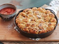 These pull-apart garlic knots are baked in a cast iron skillet for a crisp, golden brown bottom. They are intensely flavored with pepperoni, red pepper flakes, garlic, and two types of cheeses, and have a moist, buttery crumb. It's the kind of recipe that your guests will demand you make time and time again because they're that damn good. Good thing they're easy as well.