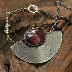 Red sapphire pendant with tribal disc backing and sterling silver chain. Original design by Sirilak Samanasak of Metal Studio Thailand. http://sirilaksamanasak.com