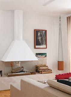 """O sofá à frente da cama se volta para a lareira (2 m x 60 cm de profundidade), com chaminé de aço e base de limestone com metal e vidro. """"Além de romântico, é um privilégio adormecer vendo as chamas"""", diz Tania."""