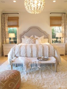 Glam bedroom. I'm loving the shade/drape combo, the beautiful textured bedding, that gorgeous headboard and lovely chandelier.