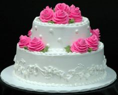 Two tier white buttercream iced cake with delicate scrolling and hot pink roses