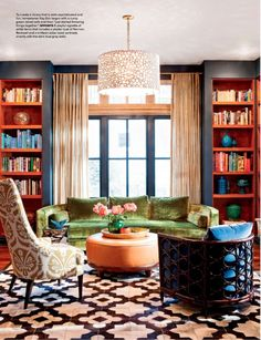 Such a colorful, eclectic mix. But it all works. Bookshelf accessories harmonize the colors. Love the bookshelf design. And the Oly chandelier.