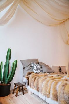 Bed with fur throw, ceiling canopy, and a cactus decor creates a bohemian space.