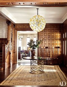 The wood-paneled entrance hall of a grand Boston townhouse is illuminated by a cheerful, spherical 1960s Italian light fixture from Galerie Van den Akker.