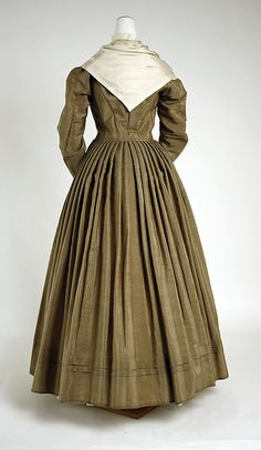 Victorian fashion dress gown from 1870 #Historical #Costume from American designer in 19th century. Made from silk and wool with decollete tie with a scarf, removable high neck, long sleeve with decorative cuff, button front and pleated long skirt with decorative hem.