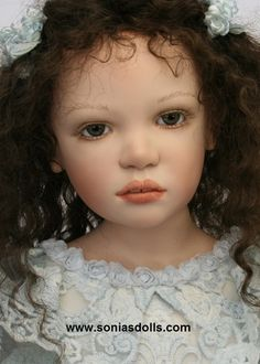 """Milena  Milena 34"""" LE 10 has dark brown, curly human hair, German mouth blow grey-blue glass eyes. She has beautifully hand painted face. Her silk light blue dress is decorated with antic laces and her stocking, sculpted porcelain boots perfectly compliment her look."""