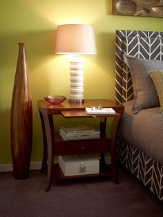 Graphic-inspired ceramic table lamps extend the aesthetic of the geometric fabric, while a classic open nightstand and wood decorative vase provide chic grounding. i love the head board!!