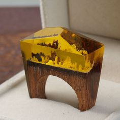 EVEN IN THE HEART OF DARKNESS, GOLD CAN STILL GLOW.  This ring is made of clear resin and flakes of real gold. The base is wenge wood, a tropical timber which is both heavy and hard.