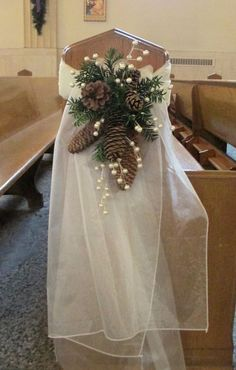 pew swag with ivory organza pine cones pine greens and berry sprigs / http://www.deerpearlflowers.com/rustic-winter-pinecone-wedding-ideas/