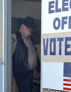 In a cellphone photo snapped by GOTV coordinator Donna Semans on October 20, county sheriff Jim Daggett is seen in the doorway of an early-voting polling place on Pine Ridge Indian Reservation, in South Dakota.