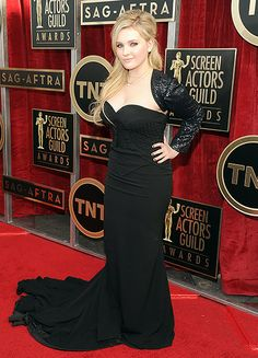 Abigail Breslin in a black, strapless sweetheart gown by Chagoury with an elaborate train. She paired her look with a lace sequin shrug in the same color.