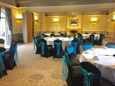 Black covers, teal sashes with silver clasps at The Manor Hotel